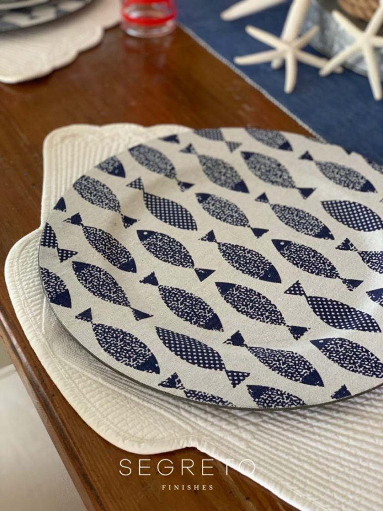 blue & white fish charger on shell placemat