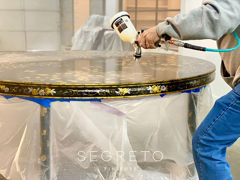 embellishing top of custom painted black table with gold leaves