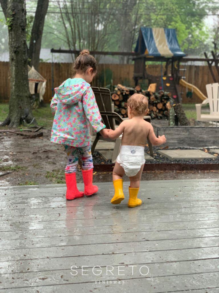 girl and baby walking in backyard