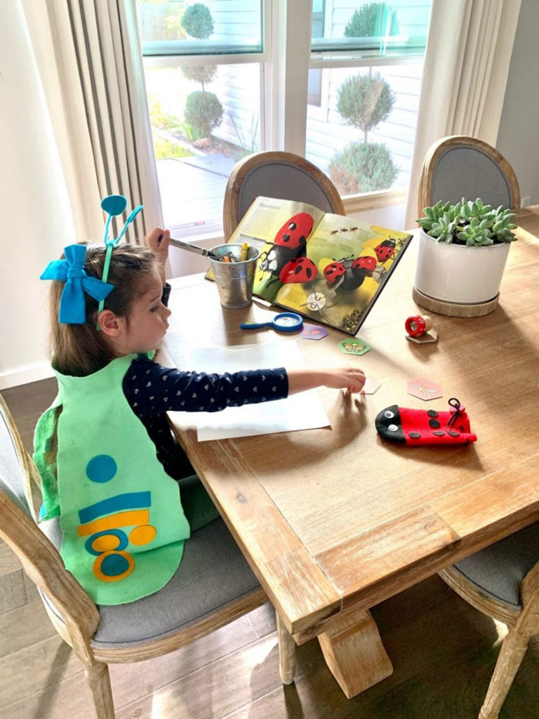 girl dressed as butterfly crafting at table