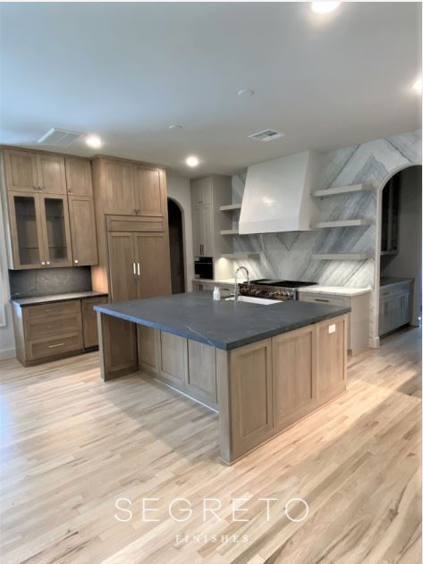 Kitchen with organic plaster hood and floating shelves, oak cabinetry