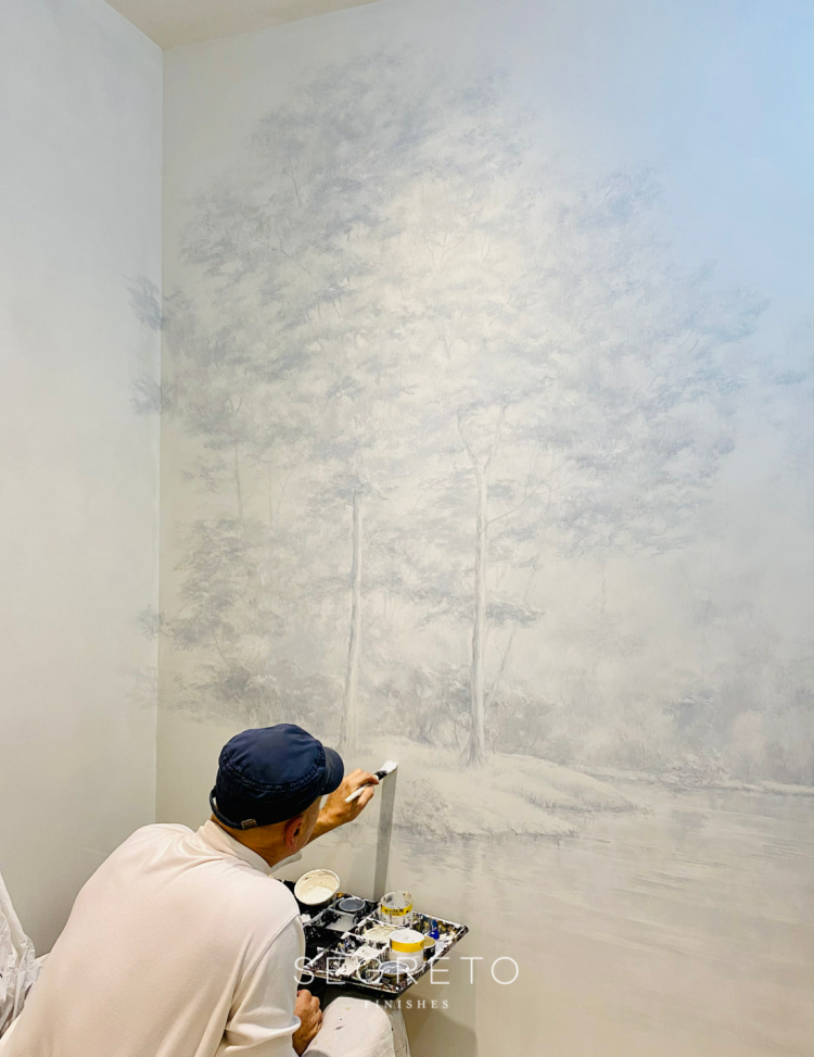 Muralist working on a mural applied over plaster