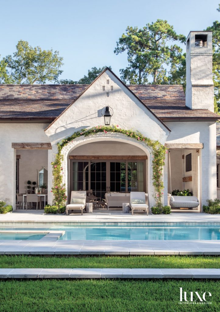 Clusters of Peggy Martin roses burst with pink blooms on a gable wall over a loggia furnished with pool-facing Janus et Cie Amari rattan chaises. The gas lantern is from Sheryl Stringer Gas Lanterns & Lighting.