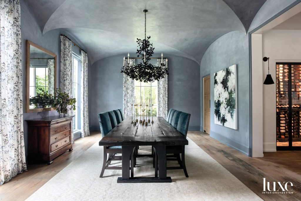 Carlos Ramirez art from Dimmitt Contemporary Art and Romo fabric draperies from Culp Associates punctuate plaster dining room walls by Segreto Finishes. A branchy chandelier from Cox London anchors a custom walnut dining table and chairs in Rose Tarlow velvet from David Sutherland. The rug is Retorra.