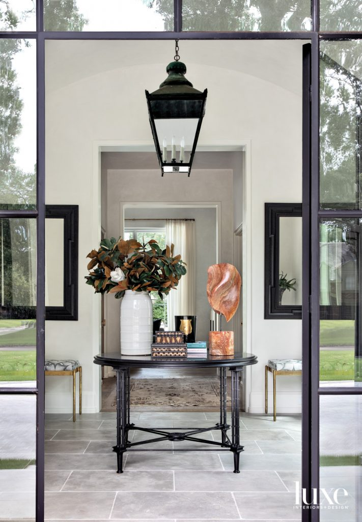 Custom steel entry doors from Atelier Domingue lead to a foyer where a 19th-century French lantern from W. Gardner Antiques lights an antique table from Shabby Slips Home and sculpture from Found. Mirrors—also from W. Gardner Antiques—overlook benches in Tillett Textiles linen. The limestone flooring is from Farmhouse Stone.