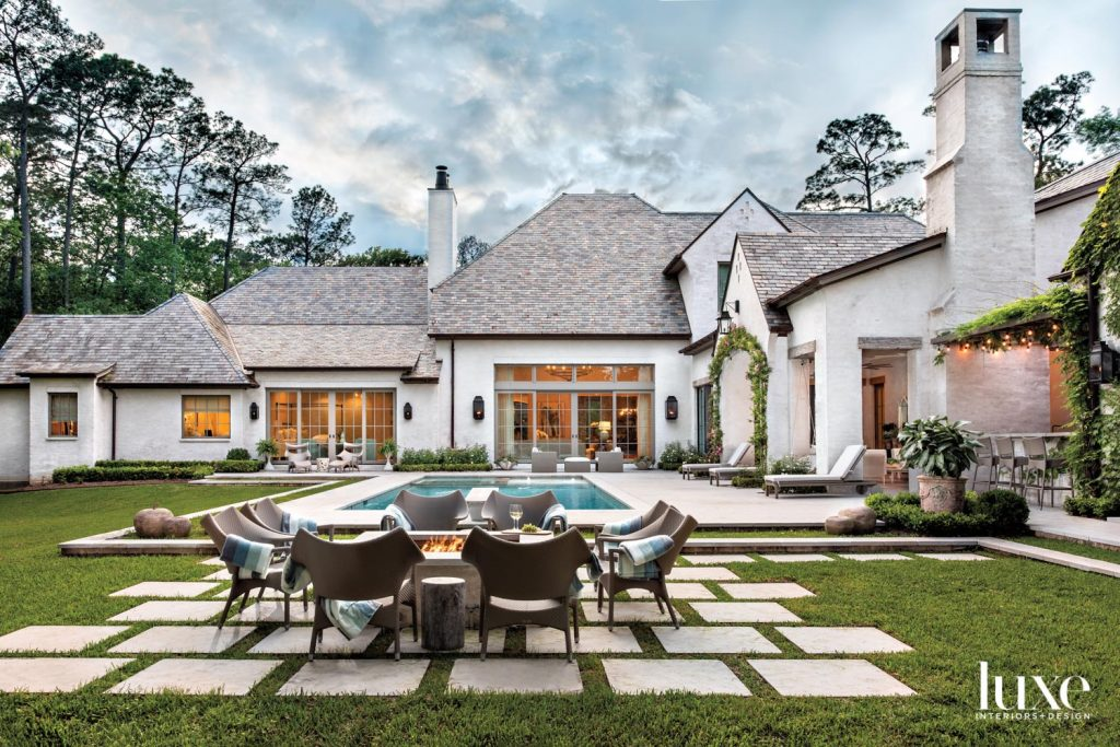 Architect Ken Newberry maintained the largest portion of the lot possible for outdoor living and wrapped the architecture around it. Janus et Cie Amari rattan armchairs surround a fire pit overlooking landscaping designed in collaboration with landscape designer Serena Gibson and installed by Kainer & Kainer Landscape Architecture. Cameron Builders, Inc. installed the pool and hardscaping.