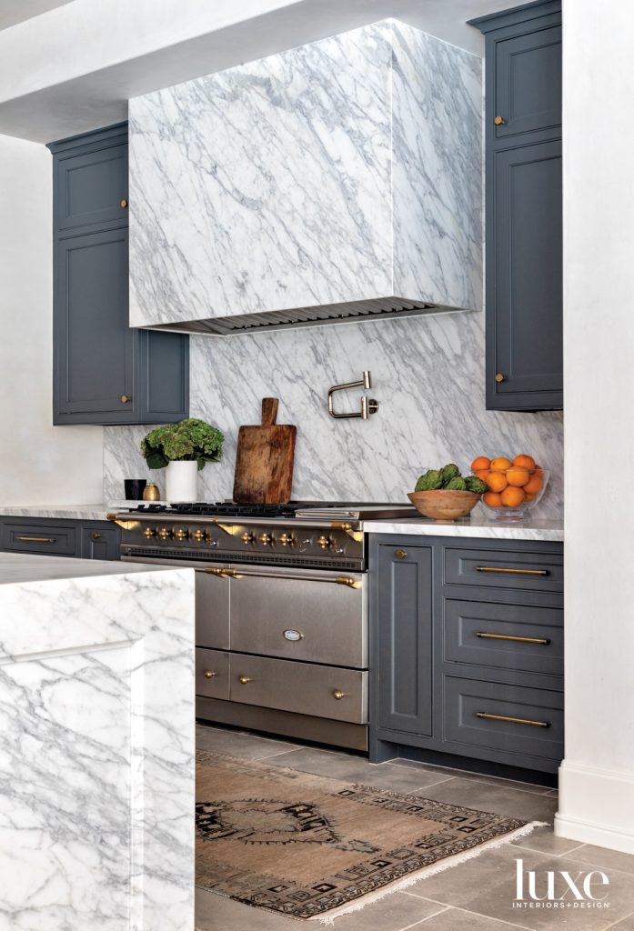 The kitchen's Calacatta marble vent hood and backsplash from Walker Zanger frame a Lacanche gas range. The rug is from Carol Piper Rugs.