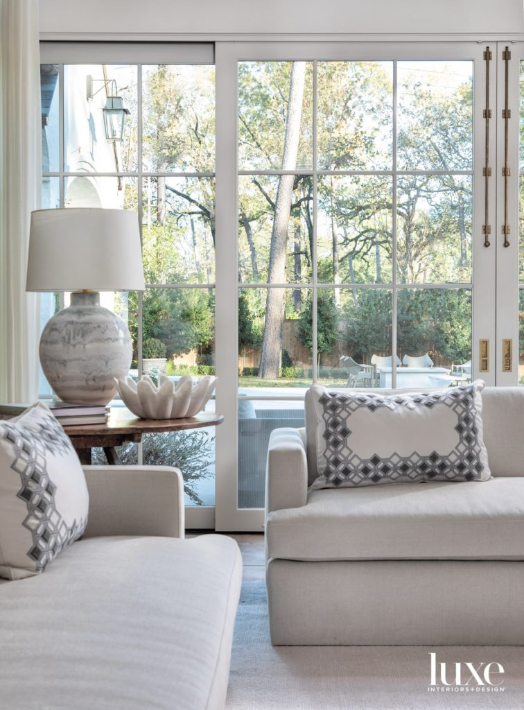 The living room's custom Belgian-style sofas in Holly Hunt fabric are accented with pillows in a Holland & Sherry custom-embroidered material. Interior designer Sheri Bailey chose a hand-blown lamp with a marble finish from Longoria Collection to top an antique walnut table from Liz Spradling Antiques.