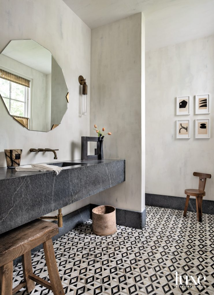The formal powder bathroom's Liaison by Kelly Wearstler Mosaics flooring from Ann Sacks echoes art by Michelle Avia from M. Naeve. A Rocky Mountain faucet from Fixtures & Fittings, Apparatus sconce and Egg Collective mirror overlook a floating soapstone sink from Arizona Tile.